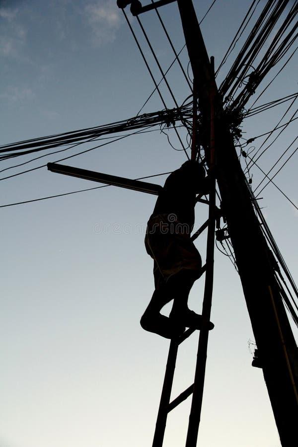 Der Mann, der die hölzerne Treppe klettert, klettern, um die Lampe zu ändern stockfoto