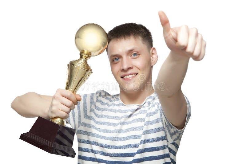 Der Mann, der einen Goldtrophäencup als Sieger in einem Wettbewerb hält, ist- lizenzfreie stockbilder