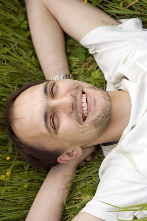 Der Mann, der einen Rest auf einem Gras hat stockfoto
