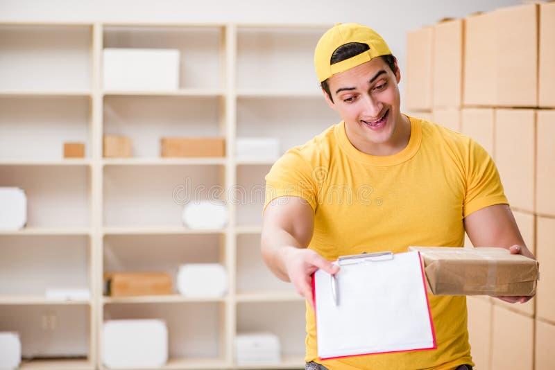 Der Mann, der im PostpaketZustelldienstbüro arbeitet lizenzfreie stockfotografie