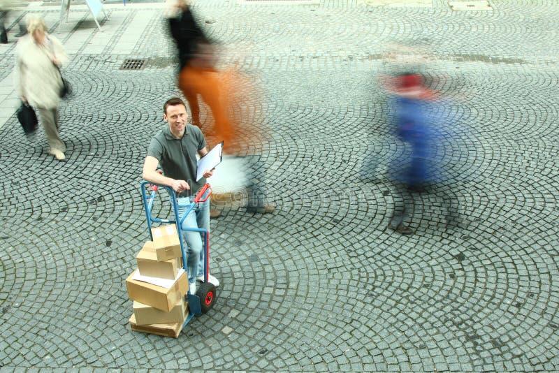 Der Mann, der mit Dolly Of Boxes While Crowd steht, geht vorbei stockfoto