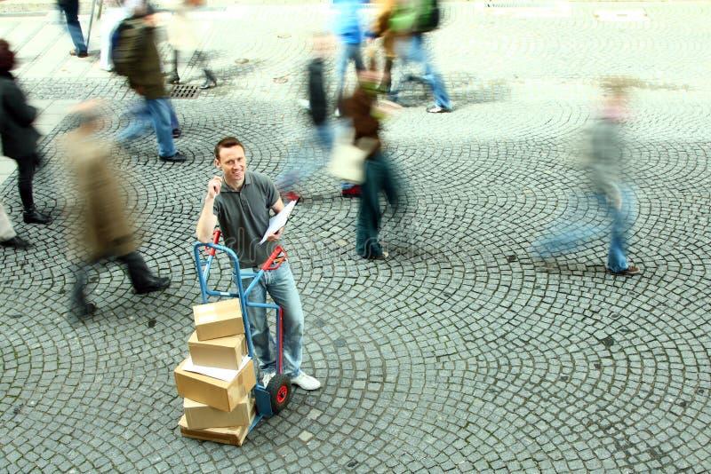 Der Mann, der mit Dolly Of Boxes While Crowd steht, geht vorbei lizenzfreies stockbild