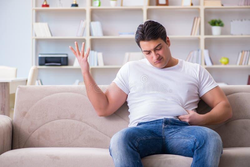 Der Mann, der unter Extragewicht im Diätkonzept leidet lizenzfreie stockfotos