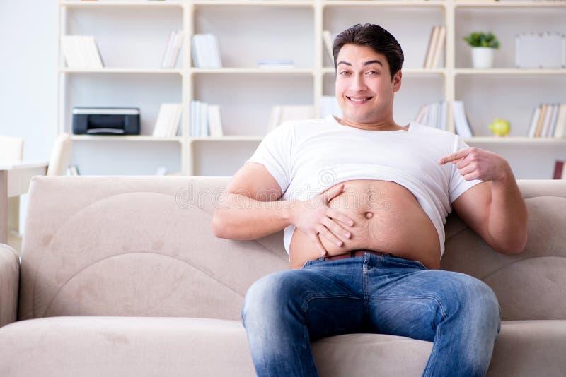 Der Mann, der unter Extragewicht im Diätkonzept leidet stockfotos