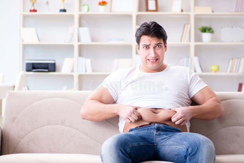 Der Mann, der unter Extragewicht im Diätkonzept leidet lizenzfreie stockfotografie