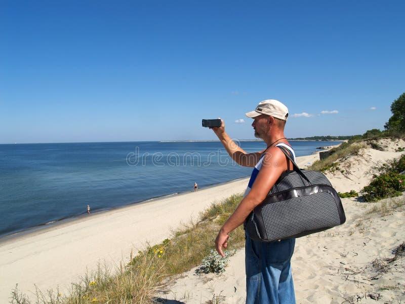 Der Mann entfernt Küste des baltischen Zopfs auf einer Video Kamera lizenzfreie stockbilder