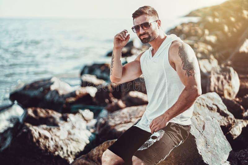 Der Mann am Erholungsort in einem weißen Hemd und in Sonnenbrille, die auf einem Felsen auf dem Seehintergrund sitzen stockfotografie