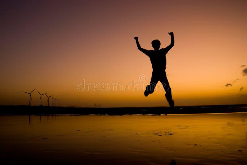 Der Mann erregte Sprung auf dem Strand unter Sonnenuntergang stockfoto