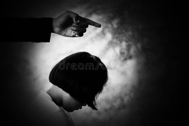 Der Mann, der Finger auf Kind zeigt, drücken und hoffnungsloses Kind mit unterem Kopf nieder stockfotografie