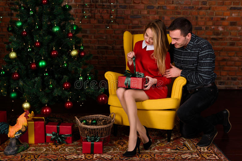 Der Mann gibt ein Geschenkmädchen nahe dem Weihnachtsbaum lizenzfreie stockfotografie