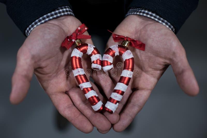 Der Mann hält eine Weihnachtsspielzeug-Zuckerstange lizenzfreies stockbild