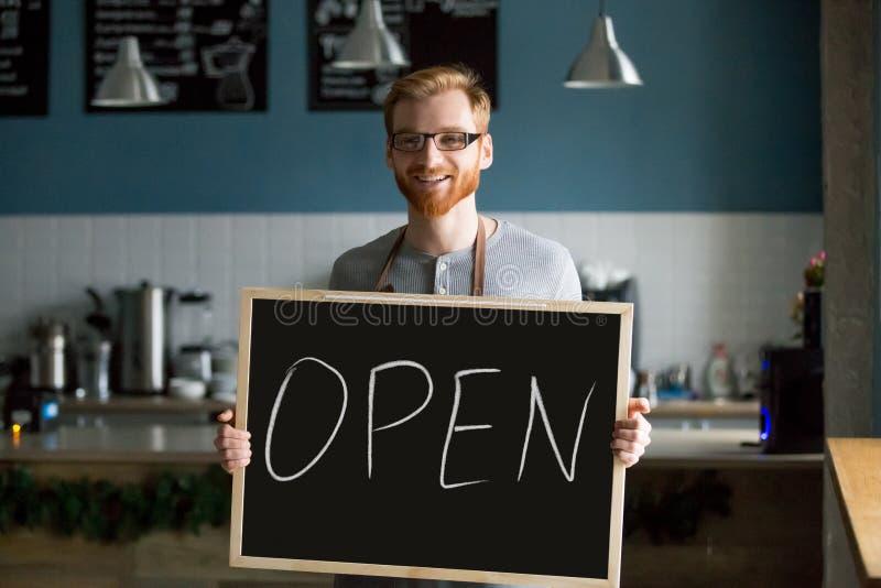 Der Mann-Holding der Rothaarigen lächelndes offenes Zeichen, das zum neuen Café einlädt lizenzfreie stockfotos
