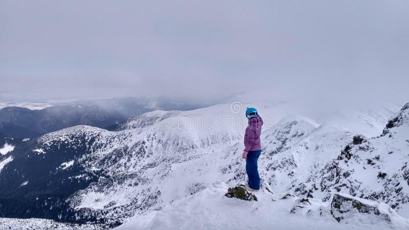 Der Mann im Blauhelm und rosa Jacke gegen einen Hintergrund von Schnee-mit einer Kappe bedeckten Bergen lizenzfreies stockbild