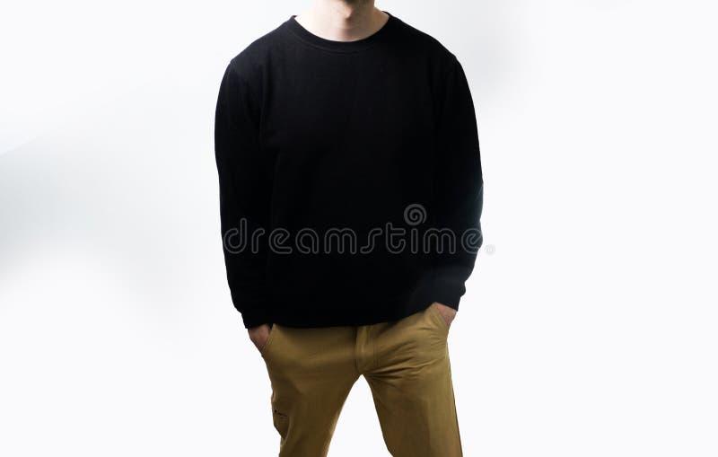 Der Mann im leeren schwarzen Hoodie, Sweatshirt, Stand, auf einem weißen Hintergrund lizenzfreies stockbild