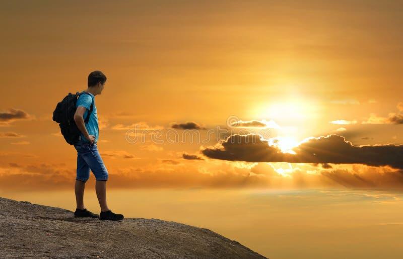 Der Mann ist auf Felsen Sonnenuntergang über Erde genießend lizenzfreie stockfotos