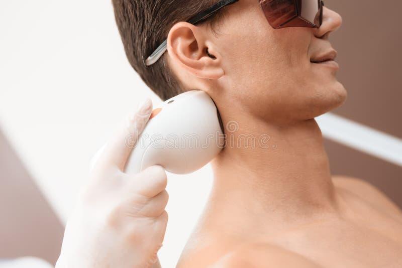 Der Mann kam zum Verfahren des Laser-Haarabbaus Der Doktor behandelt seine Schultern, Hals und Rückseite mit einem speziellen App lizenzfreie stockbilder