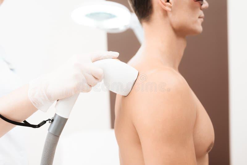 Der Mann kam zum Verfahren des Laser-Haarabbaus Der Doktor behandelt seine Schultern, Hals und Rückseite mit einem speziellen App stockfotografie
