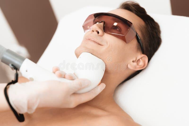 Der Mann kam zum Verfahren des Laser-Haarabbaus Der Doktor behandelt seinen Hals und Gesicht mit einem speziellen Apparat lizenzfreies stockbild