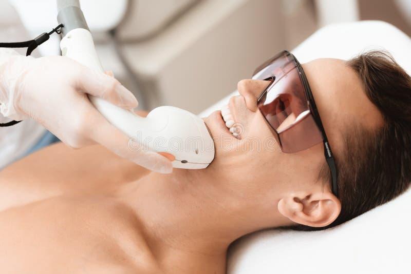Der Mann kam zum Verfahren des Laser-Haarabbaus Der Doktor behandelt seinen Hals und Gesicht mit einem speziellen Apparat lizenzfreie stockfotografie