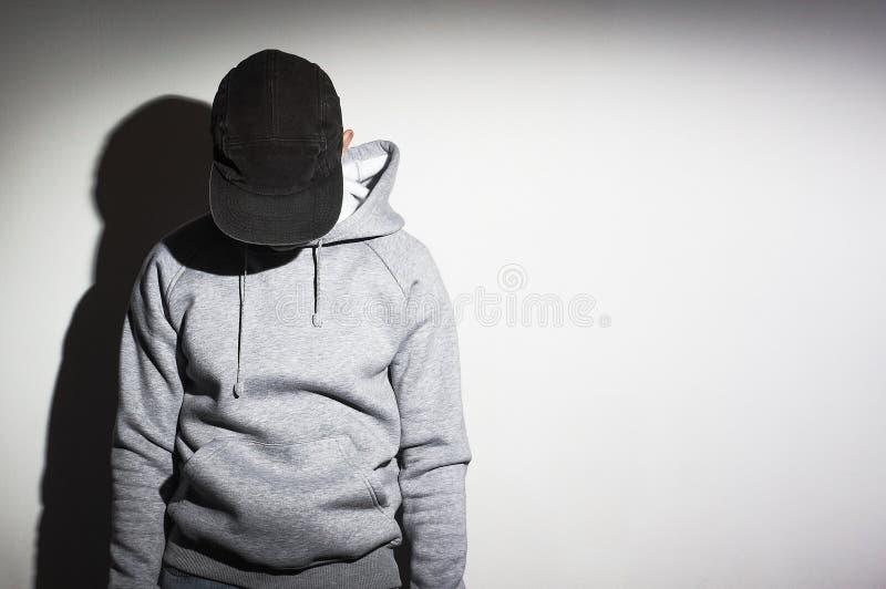 Der Mann, Kerl im leeren Schwarzen, Baseballmütze, grauer Kapuzenpulli lizenzfreie stockfotografie