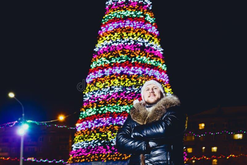 Der Mann in der Lederjacke mit Pelz nahe dem Weihnachtsbaum lizenzfreie stockbilder