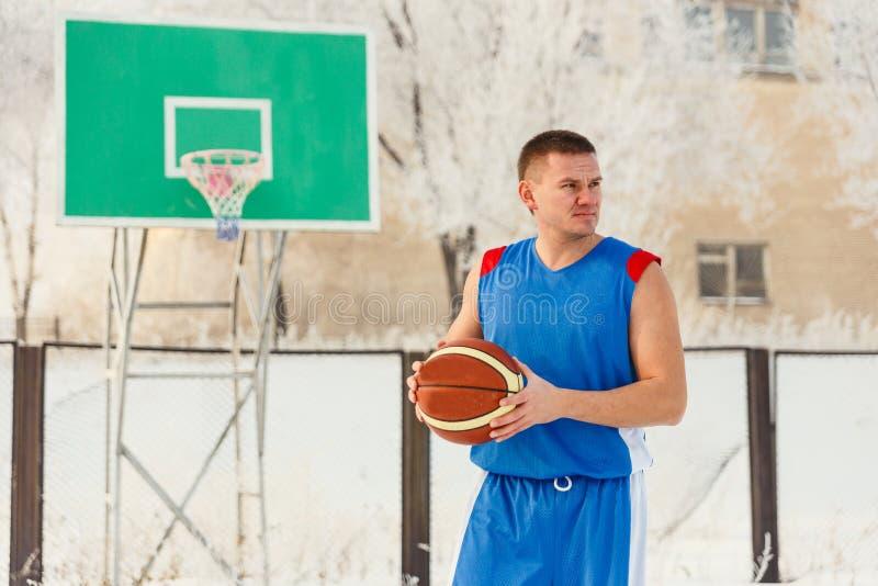 Der Mann mit dem Basketball draußen auf dem Spielplatz stockbilder