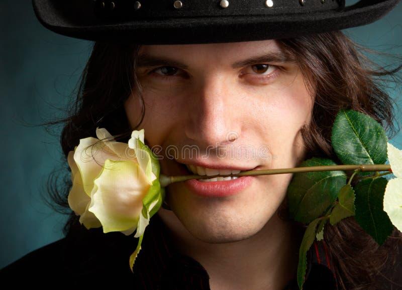 Der Mann mit einer Rose in Zähne lizenzfreie stockfotos