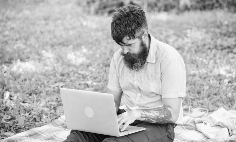 Der Mann, der mit Laptop b?rtig ist, sitzen Wiesennaturhintergrund Blogger, der von Natur aus angespornt wird Verfassersuchen stockbild
