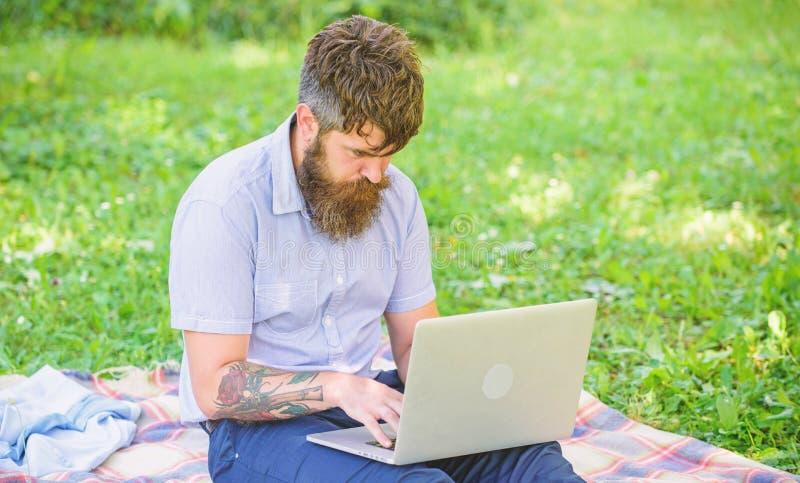 Der Mann, der mit Laptop b?rtig ist, sitzen Wiesennaturhintergrund Blogger, der von Natur aus angespornt wird Verfassersuchen stockfotografie