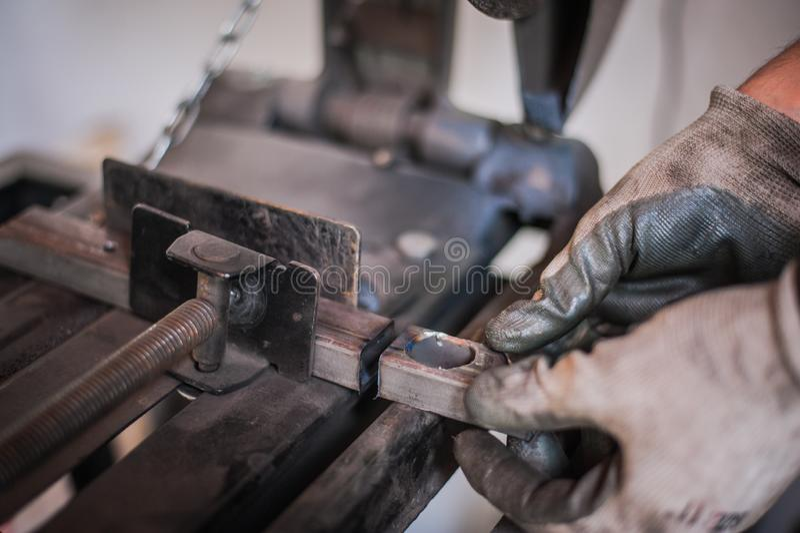 Der Mann mit Schutzhandschuhen hält das geschnittene Metall, nachdem er gerieben hat stockfotografie