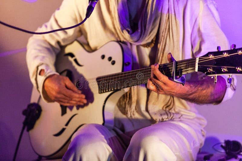 Der Mann, der nur Weiß trägt, ist das Spielen Live auf einer fantastischen weißen Gitarre mit Capo stockfoto