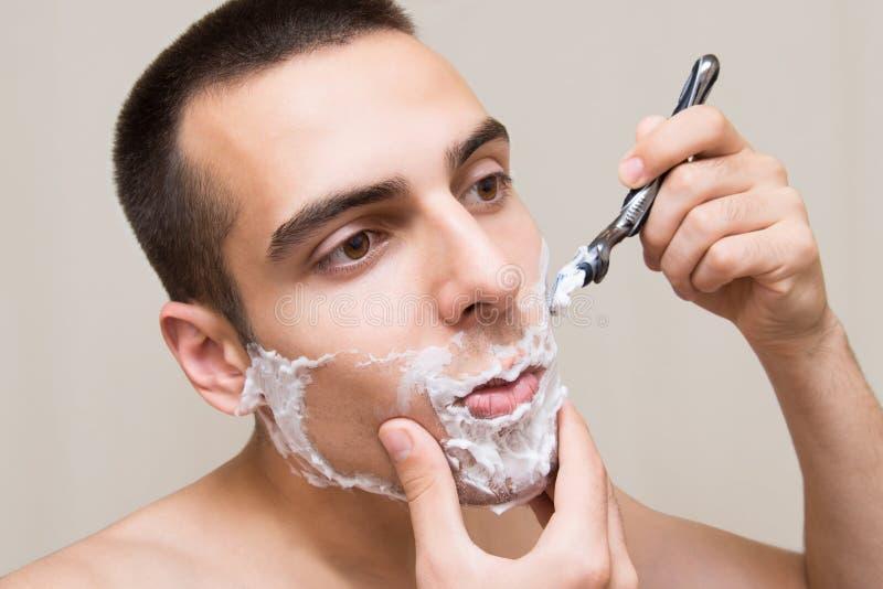 Der Mann rasiert sich stockfotos