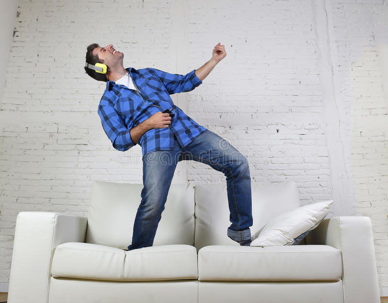 der Mann 20s oder 30s sprang auf Couch hörend Musik am Handy mit den Kopfhörern, die Luftgitarre spielen lizenzfreies stockbild