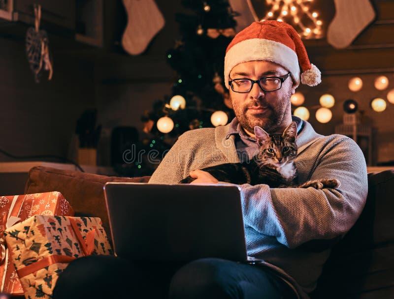 Der Mann in Sankt-Hut und -gläsern, die in der warmen Strickjacke gekleidet werden, hält Katze und mit Laptop Weihnachten zu Haus lizenzfreie stockfotos