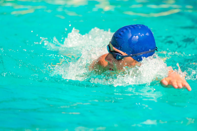 Der Mann schwimmt schnell im Pool lizenzfreie stockfotografie