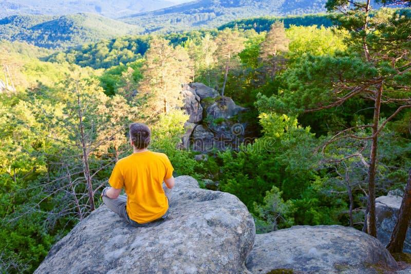 Der Mann sitzt auf dem Berg stockfoto