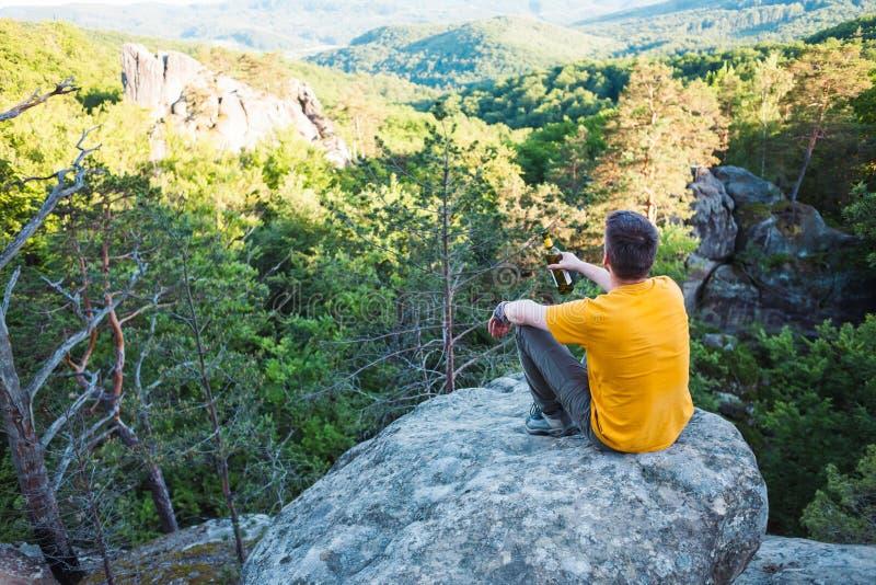 Der Mann sitzt auf dem Berg lizenzfreie stockfotografie