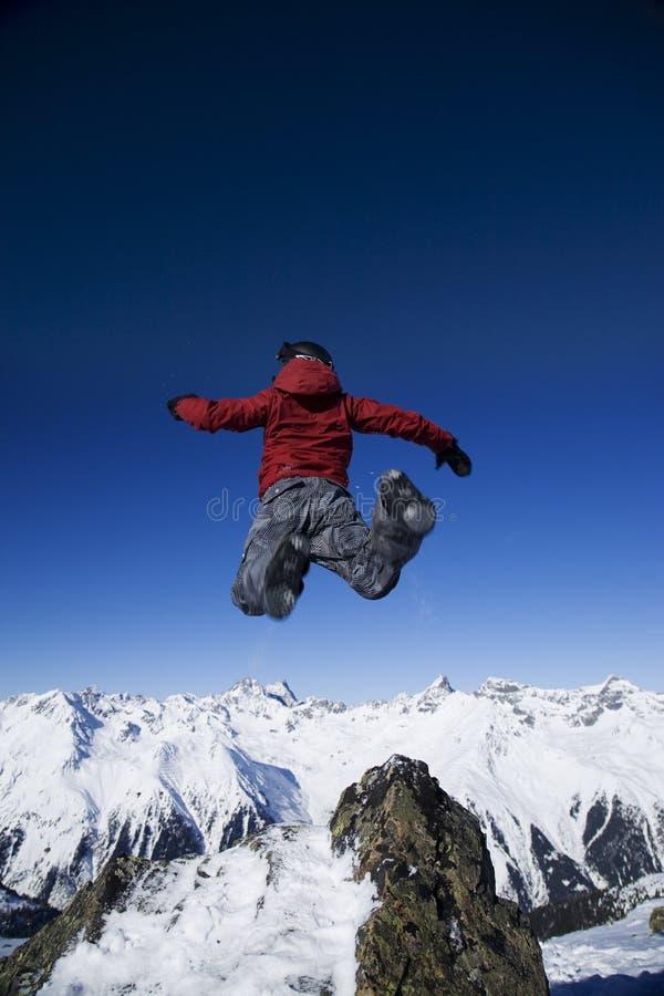 Der Mann springend über die Berge stockfotos