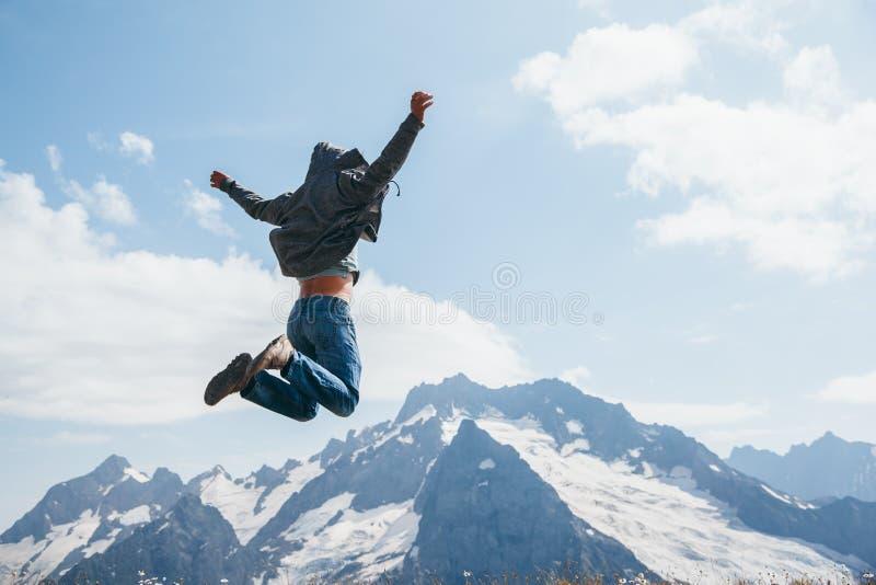 Der Mann springend auf Berg stockbilder