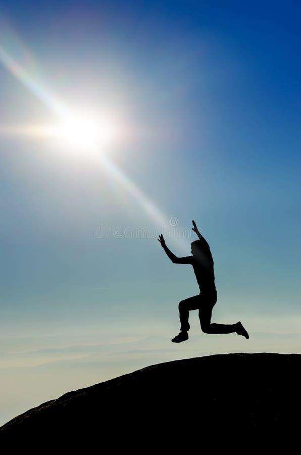 Der Mann springend auf Bergspitzeschattenbild stockfotografie
