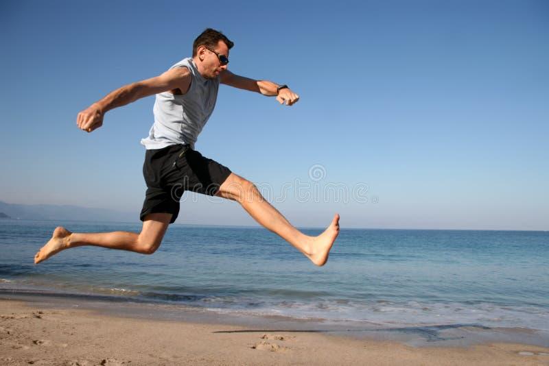 Der Mann springend auf den Strand stockbild