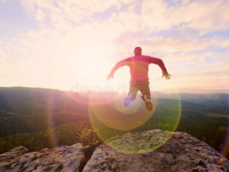 Der Mann springend vom Gebirgsrand Der Mann springend weg von einer Klippe ohne Seil Riskanter Moment stockbilder