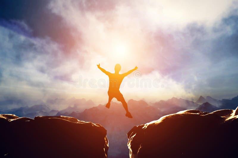 Der Mann springend zwischen zwei Berge bei Sonnenuntergang lizenzfreie abbildung