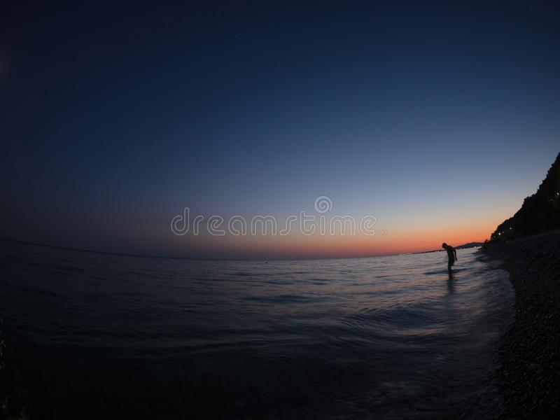 Der Mann stieg in das Wasser auf dem Strand nachts ein stockfotografie