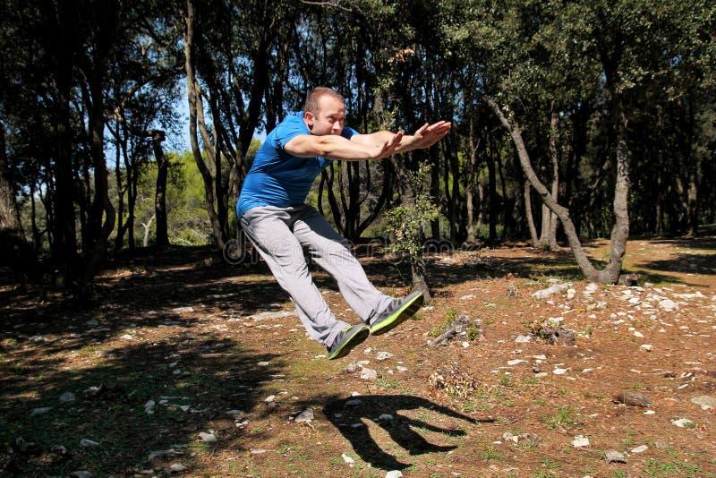 Der Mann, der Trainingssprung oben in der Luftübung in tragender Sportkleidung des Waldhübschen Sportlers tut, springt oben in Lu lizenzfreie stockfotos