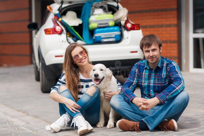 Der Mann und die Frau mit dem Hund mit dem Auto bereit zur Autoreise stockfotografie