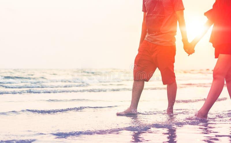 Der Mann und die Frauen halten eine ` s Hand auf dem Strand und der Front des Sonnenuntergangs das rote Kleid der Frauenabnutzung stockfoto