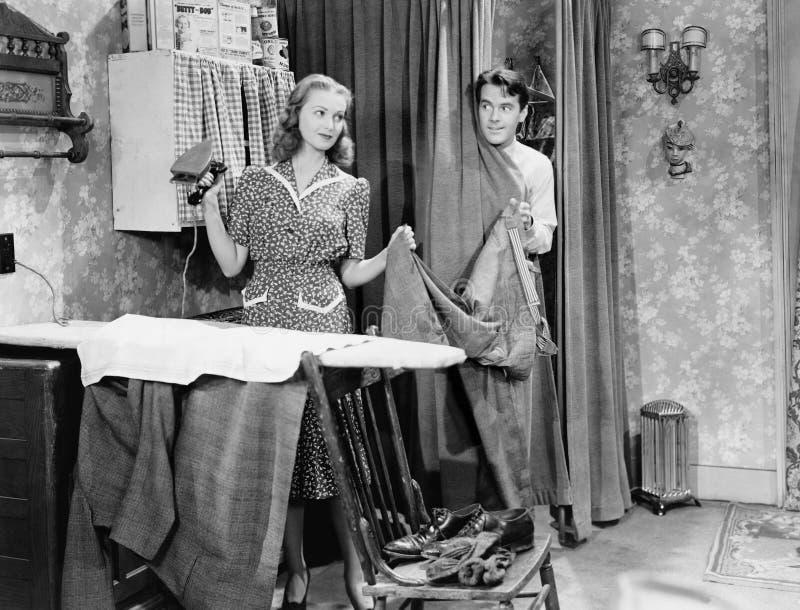 Der Mann und Frau, die in einer Küche stehen, während sie seine Hosen bügelt und in ihm ist hinter einem Vorhang (alle dargestell stockbild