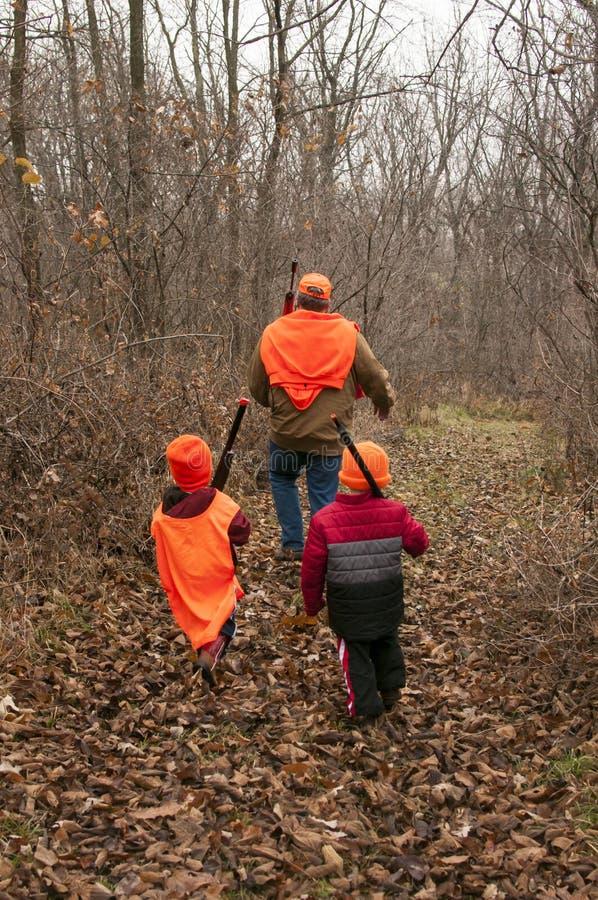 Der Mann und Jungen, die mit ihren Gewehren auf einem Praxisrotwild gehen, jagen lizenzfreies stockfoto