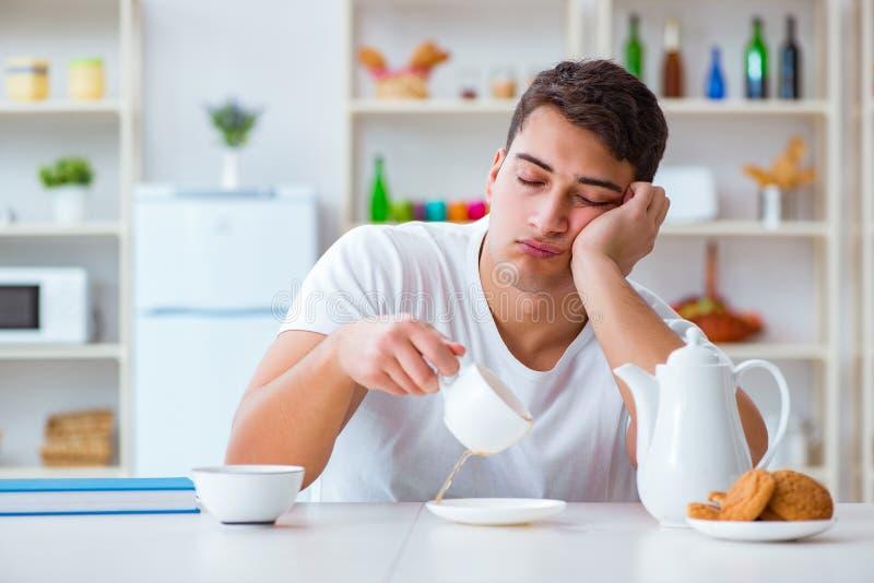 Der Mann, der während seines Frühstücks nach Überstundenarbeit einschläft lizenzfreie stockbilder